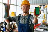 istock Young Workman Presenting Mobile App 886643358