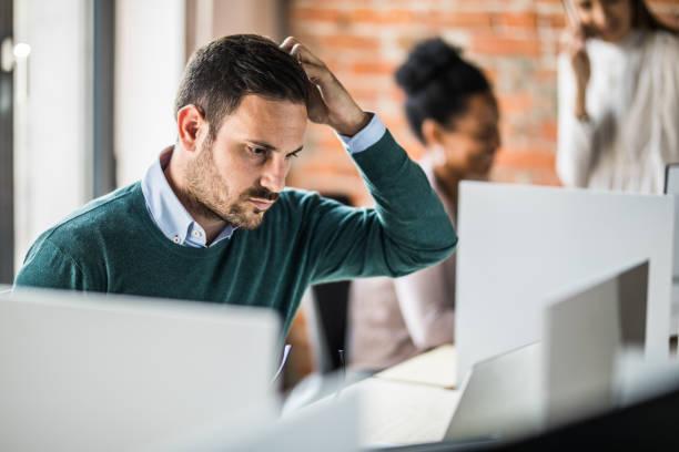 junge besorgt geschäftsmann zur unternehmenszentrale am laptop arbeiten. - verwirrung stock-fotos und bilder