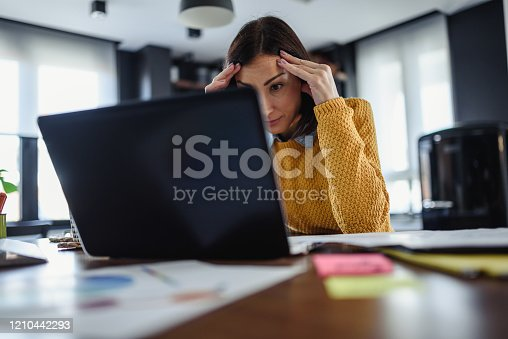 Young worried entrepreneur woman looking at laptop computer at home. Freelance woman programmer working from home