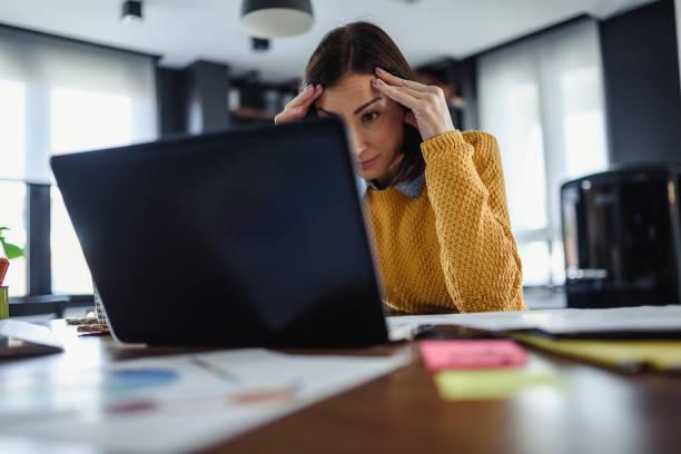 junge besorgte unternehmerin schaut auf laptop-computer zu hause - frustration stock-fotos und bilder