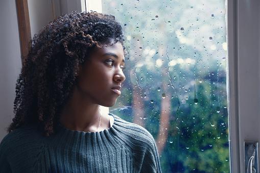Black woman feeling depression symptoms alone at home