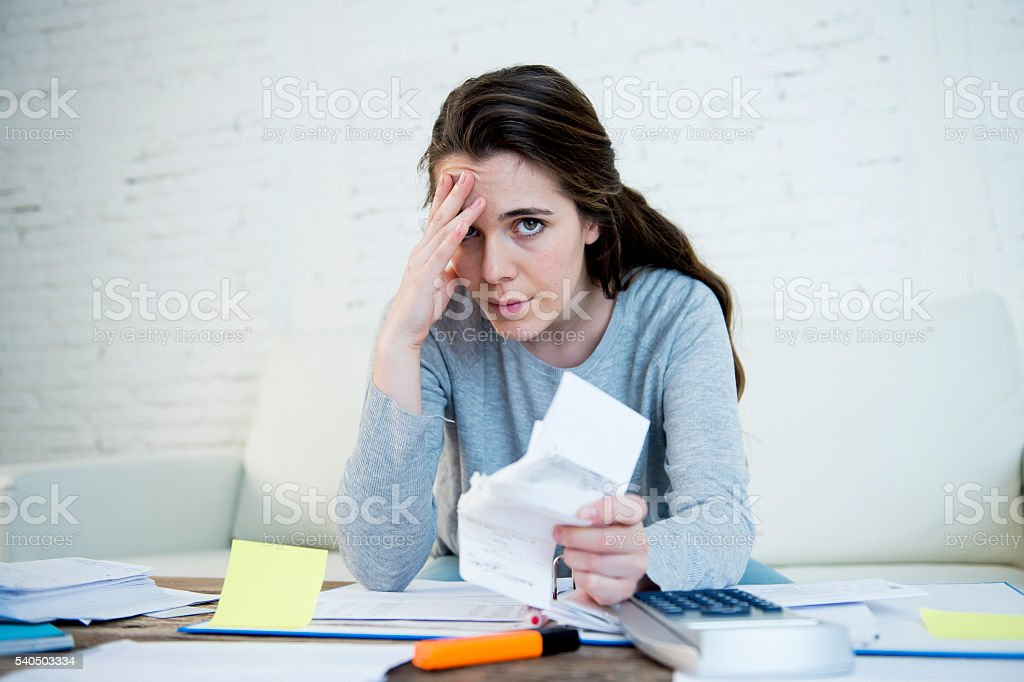 young worried woman suffering stress doing domestic accounting paperwork stock photo
