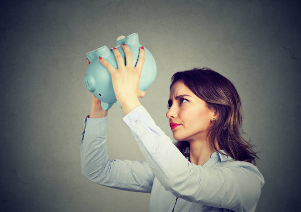 young worried woman with empty piggy bank - lost stock photos and pictures