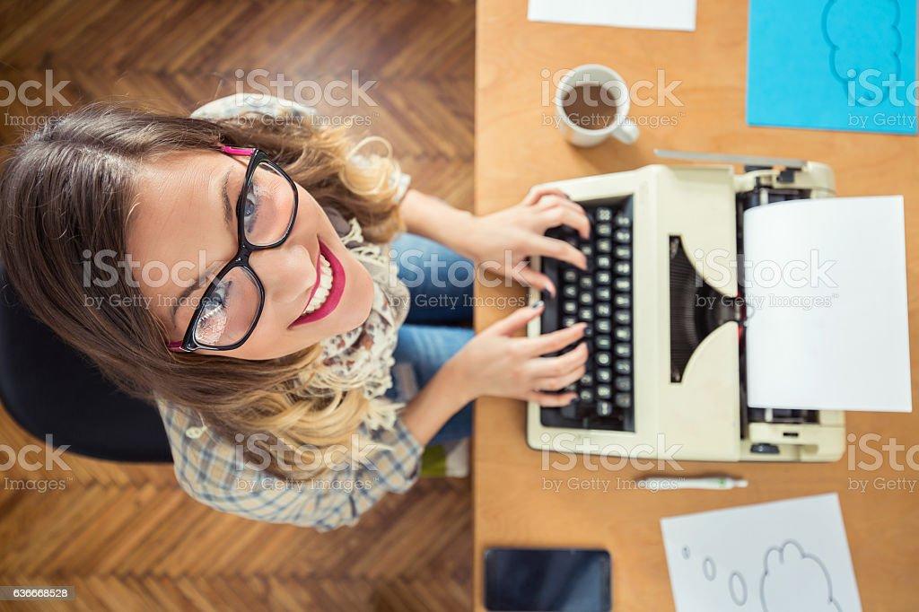Young Writer Using Typing Machine stock photo