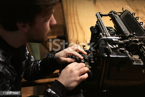 504606248 istock photo Young writer working on typewriter 1133878667