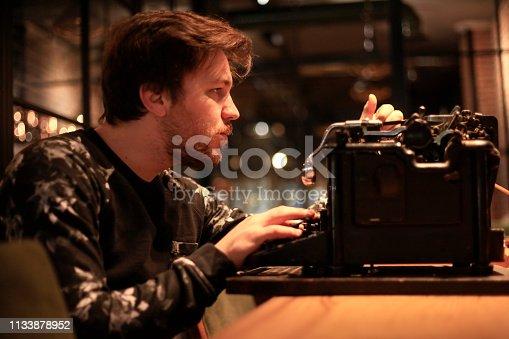 504606248 istock photo Young writer working on typewriter 1133878952