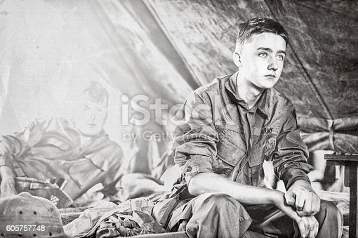 A Young WWII US Infantryman and one other soldier sitting in their tent.  Contemplating, worrying and thinking of home.
