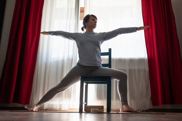 Young yoga woman doing warrior pose using chair. stock photo