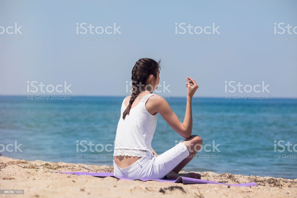 Young yoga woman meditating on the beach royalty-free stock photo
