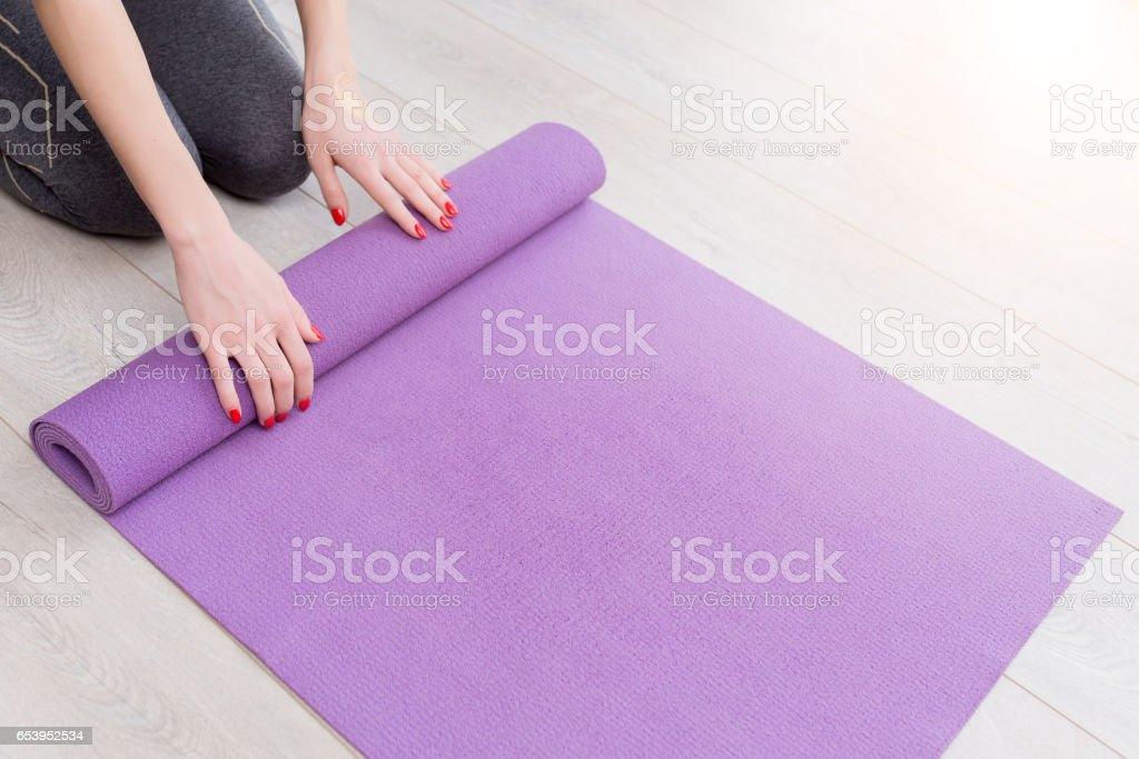 Young yoga Woman rolling her lilac mat stock photo