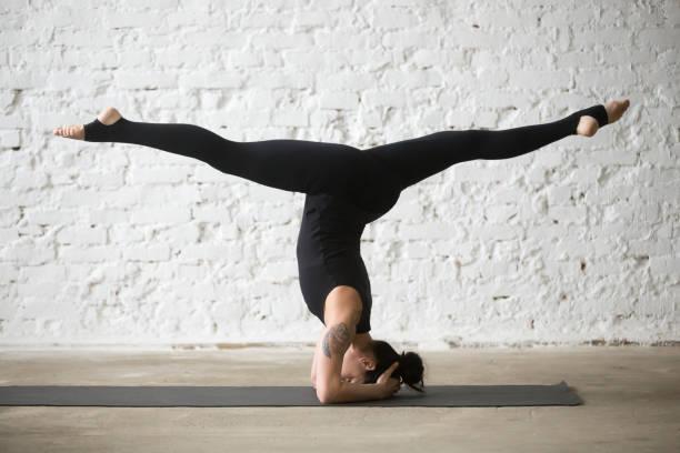 junge jogi attraktive frau, die salamba sirsasana posieren mit splitt - gymnastik tattoo stock-fotos und bilder