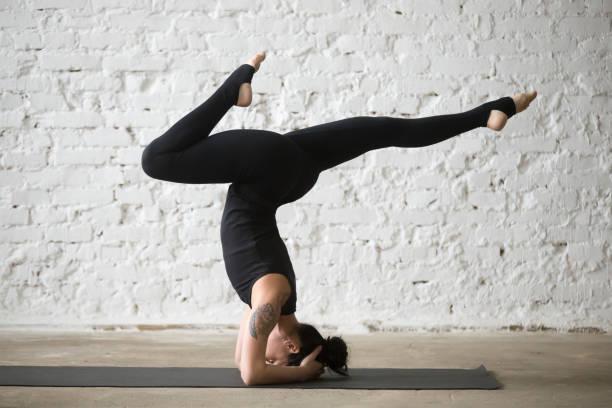 junge yogi attraktive frau, die unterstützende kopfstand-pose variation - gymnastik tattoo stock-fotos und bilder