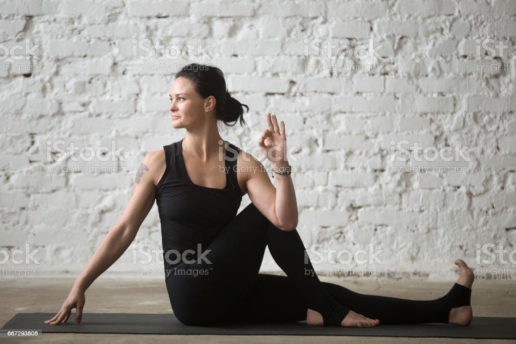 Young yogi attractive woman in Ardha Matsyendrasana pose, white loft stock photo
