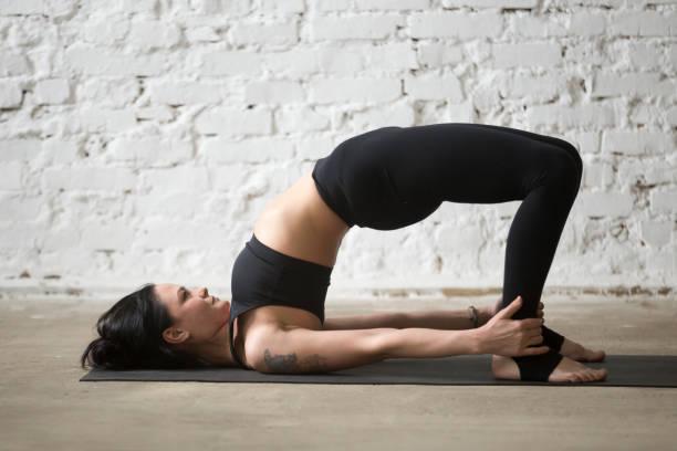 junge jogi attraktive frau in glute bridge posieren, loft hintergrund - gymnastik tattoo stock-fotos und bilder