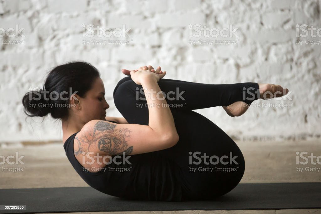 Young yogi attractive woman in Knees to Chest pose, studio stock photo