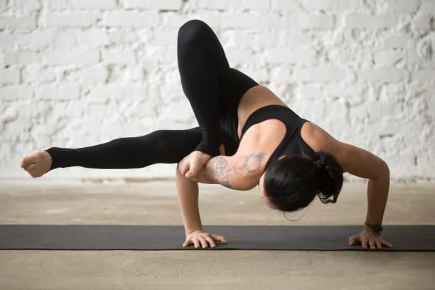 attraktive frau junge yogi in maksikanagasana pose, weiße loft hintergrund - gymnastik tattoo stock-fotos und bilder