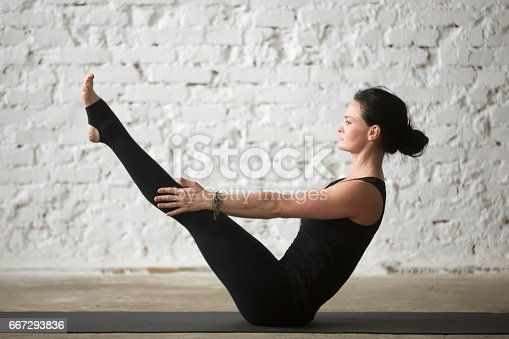 914755474 istock photo Young yogi attractive woman in Paripurna Navasana pose, white background 667293836
