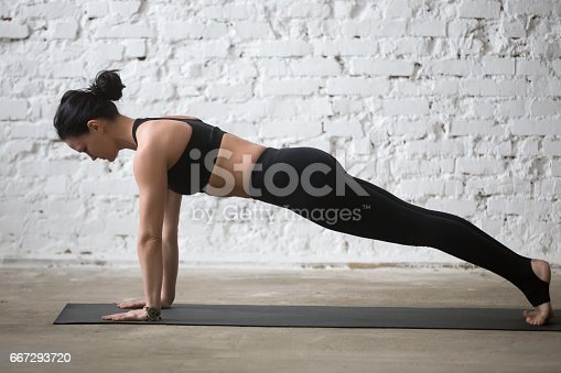 675173150 istock photo Young yogi attractive woman in Plank pose, white loft background 667293720