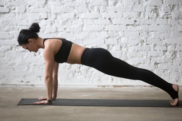 young yogi attractive woman in plank pose, white loft background - peso mosca foto e immagini stock