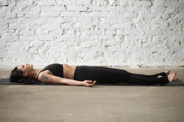attraktive frau junge yogi in savasana pose, weiße loft hintergrund - gymnastik tattoo stock-fotos und bilder