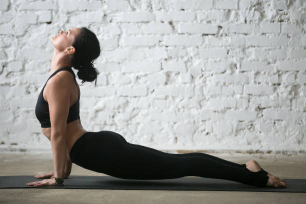 Young yogi attractive woman in upward facing dog pose, studio Mid aged yogi attractive woman practicing yoga concept, stretching in upward facing dog exercise, Urdhva mukha shvanasana pose, working out wearing black sportswear, full length, white loft background upward facing dog position stock pictures, royalty-free photos & images