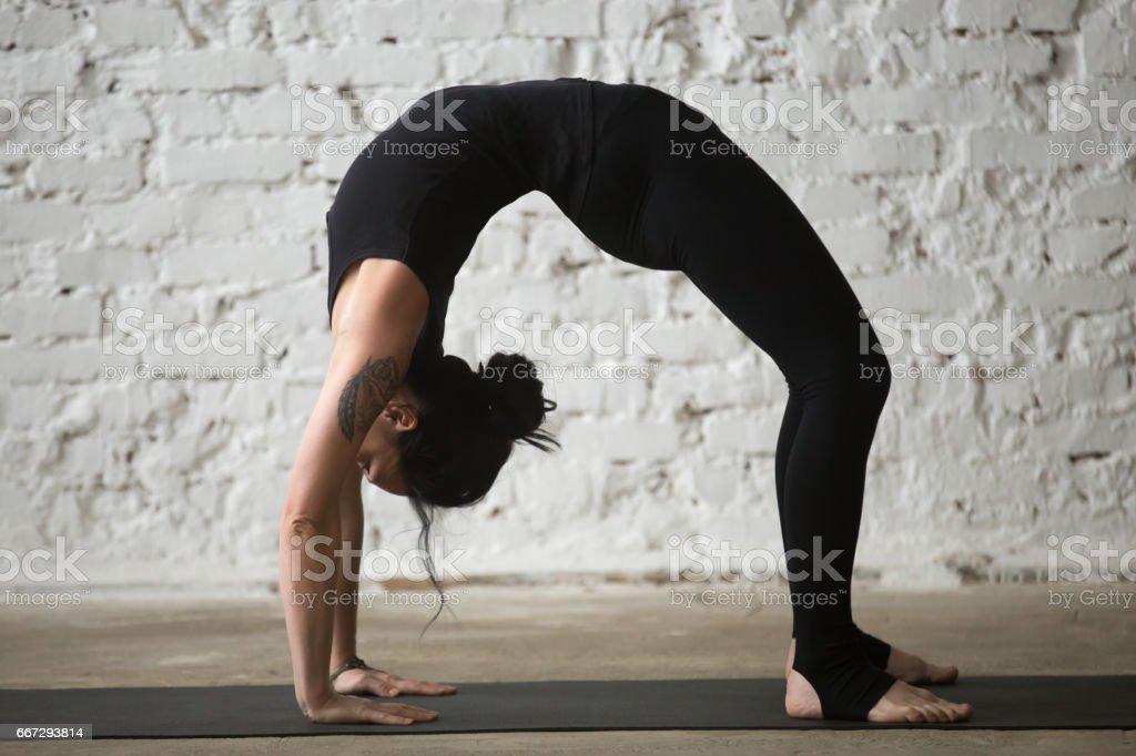 Young yogi attractive woman in Urdhva Dhanurasana pose, loft background stock photo