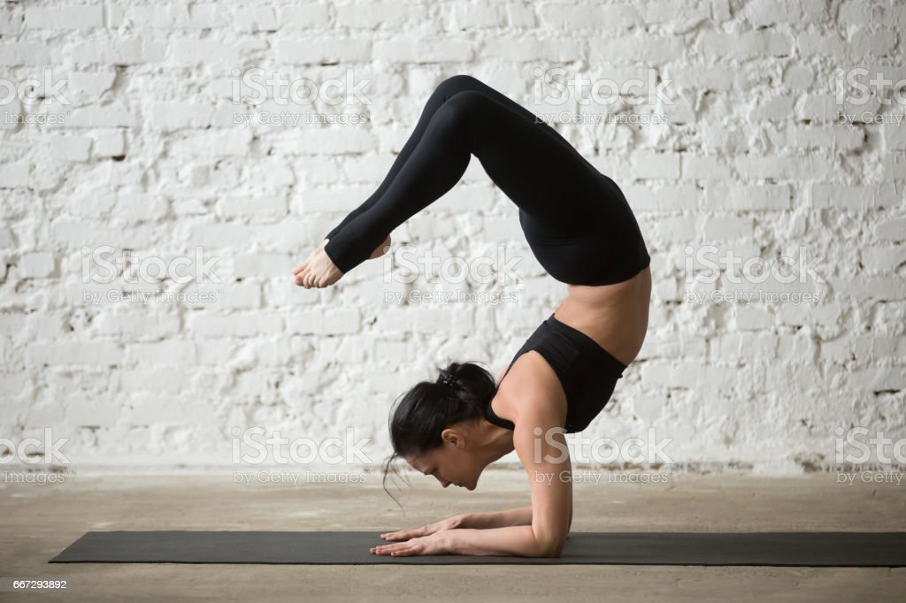 Young yogi attractive woman in vrischikasana pose, white loft background stock photo
