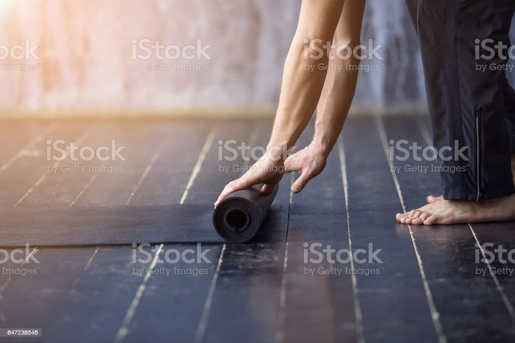 Young yogi men rolling mat stock photo