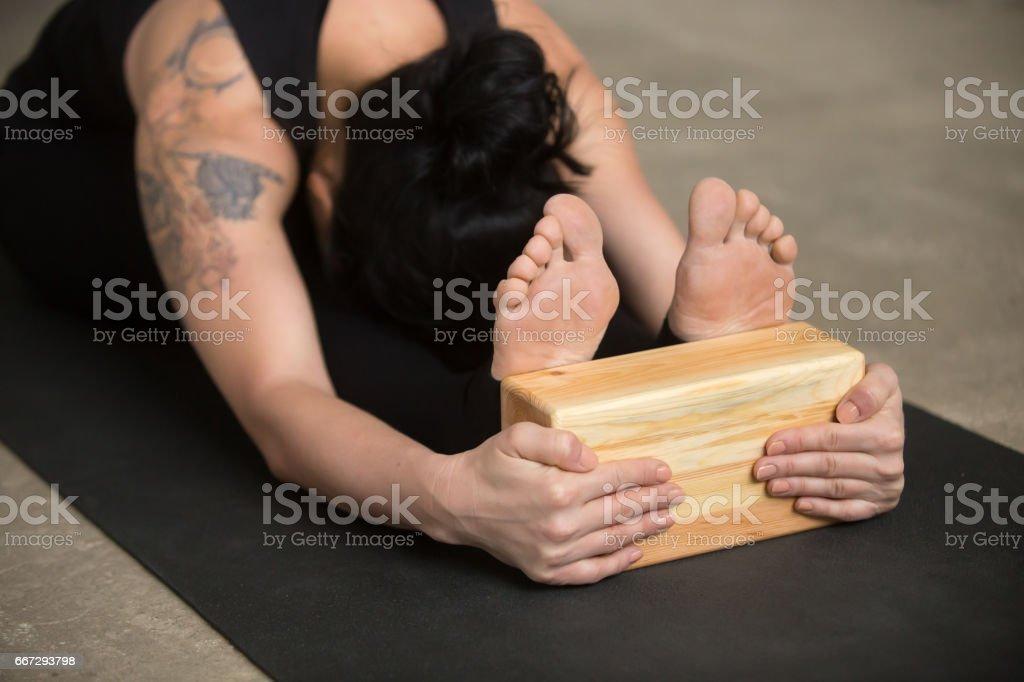 Young yogi woman in paschimottanasana pose with block, close up stock photo