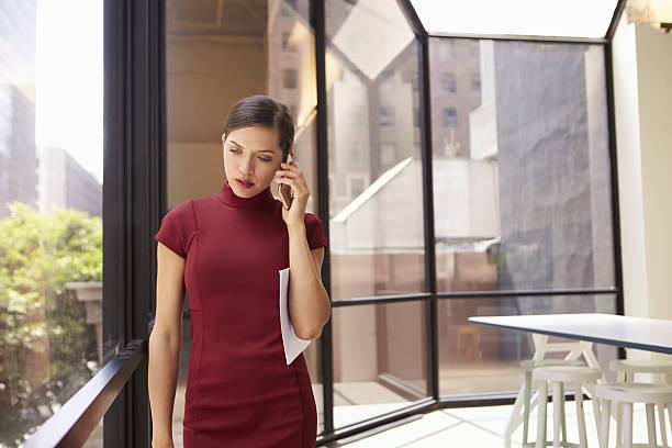 young young white businesswoman using phone in modern office - enge kleider stock-fotos und bilder