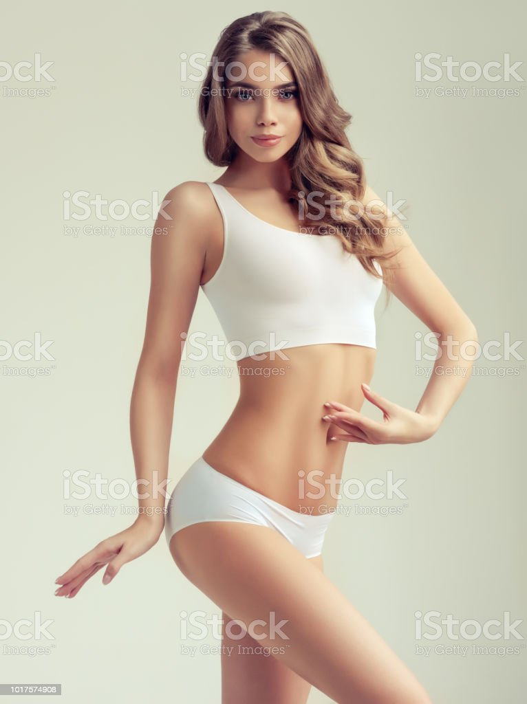 cad2b5e035064 Young Young woman with graceful and slim body dressed in a white sport  underwear. Elegant gesture and healthy, perfect figure. - Stock image .