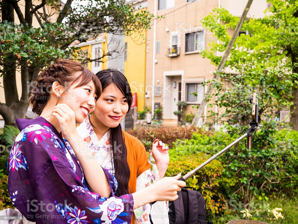 Young yukata women taking picture with smart phone, selfie stock photo