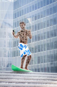 Young zombie (businessman) surf with smart phone outside office - Needs vacations ! Escape from the work
