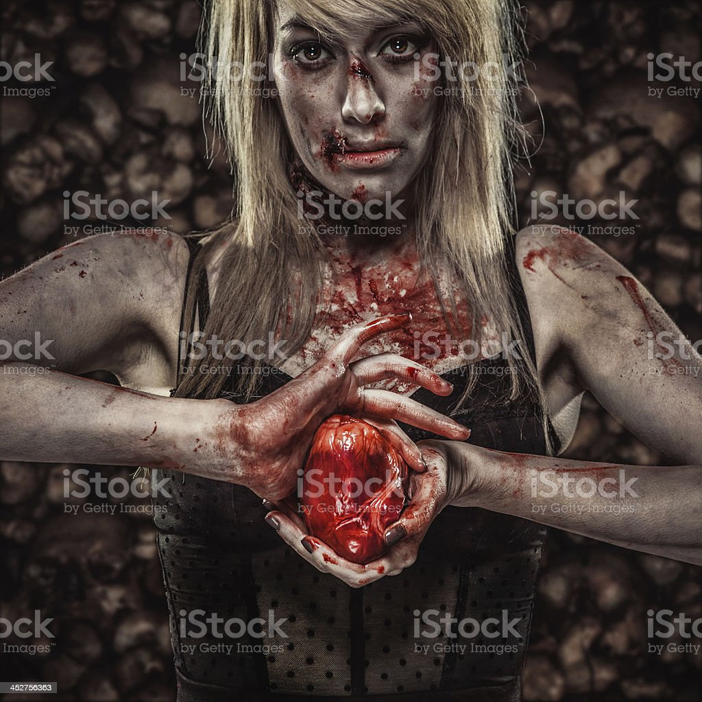 Young Zombie Woman Holding a Human Heart stock photo