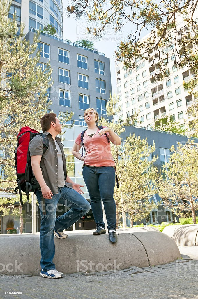 Younge backpackers couple walking downtown - II royalty-free stock photo