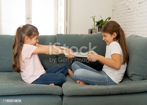 istock Younger and older girls fighting for laptop arguing over playing on the internet. Lifestyle portrait of sisters not sharing computer in Relationship between siblings and technology addiction concept. 1150924828