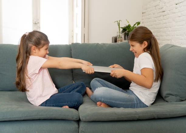Jüngere und ältere Mädchen, die um Laptop kämpfen, streiten sich über das Spielen im Internet. Lifestyle-Porträt von Schwestern, die keinen Computer in Beziehung zwischen Geschwistern und Technologie-Suchtkonzept teilen. – Foto