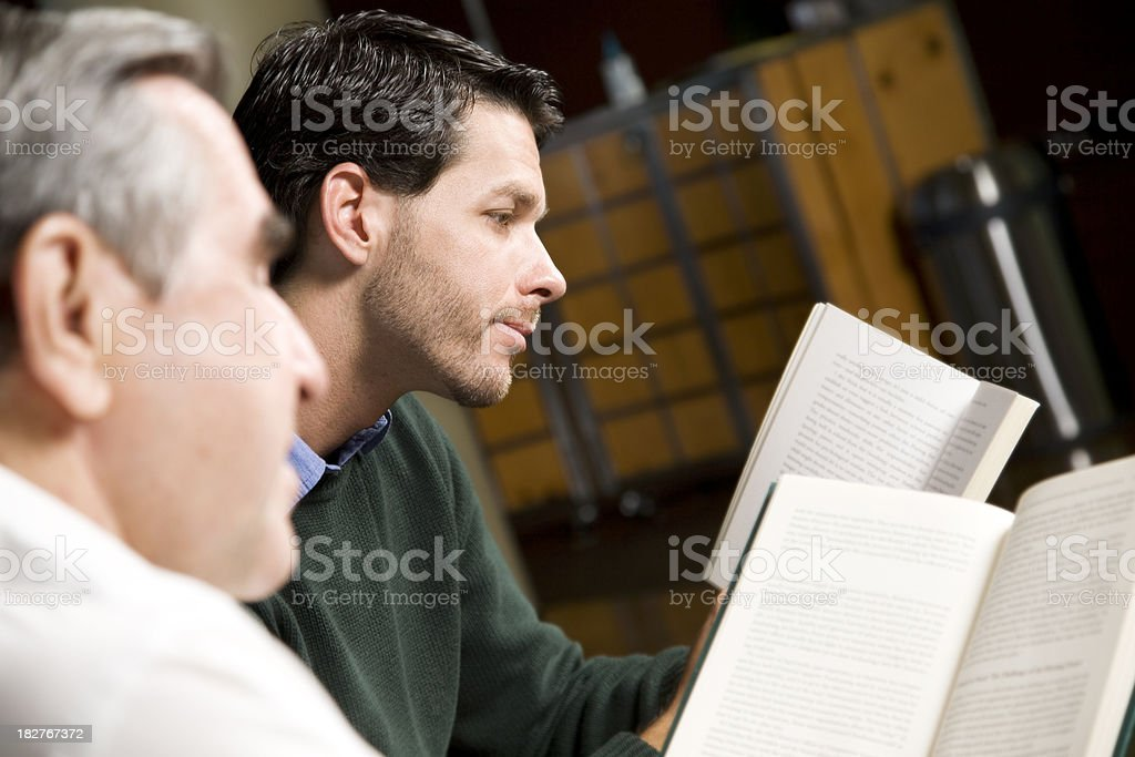 Younger and Older Man Reading Together royalty-free stock photo