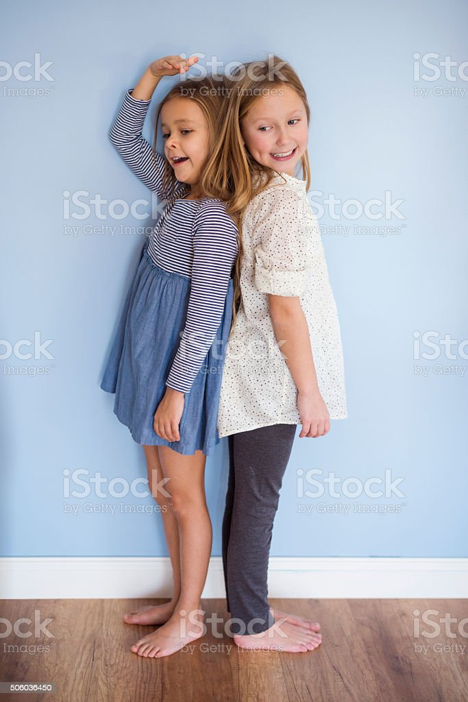 Younger girl is almost as tall as her sister stock photo