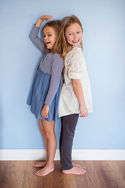 younger girl is almost as tall as her sister - height measurement stock photos and pictures