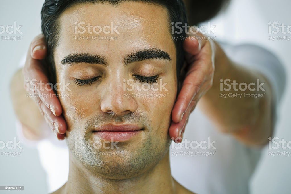 A younger man getting a head massage stock photo