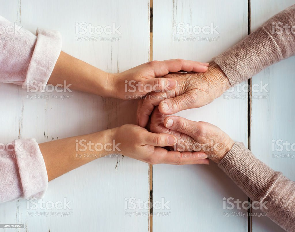 Younger woman's hands holding older woman's hands stock photo