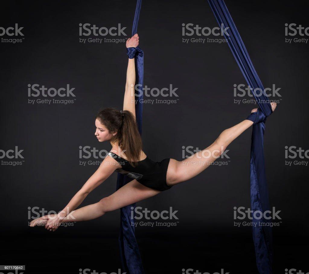 Joven, sonriendo la chica hace ejercicios en las lonas. - foto de stock