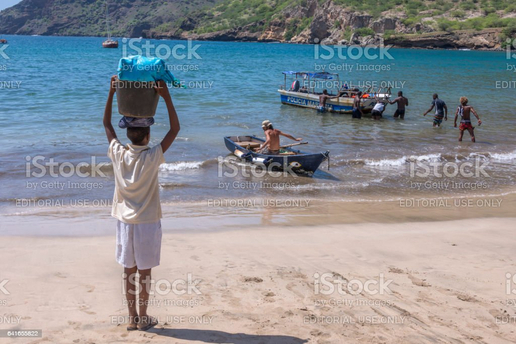 Joven observando a los pescadores en la playa de Tarrafal - foto de stock
