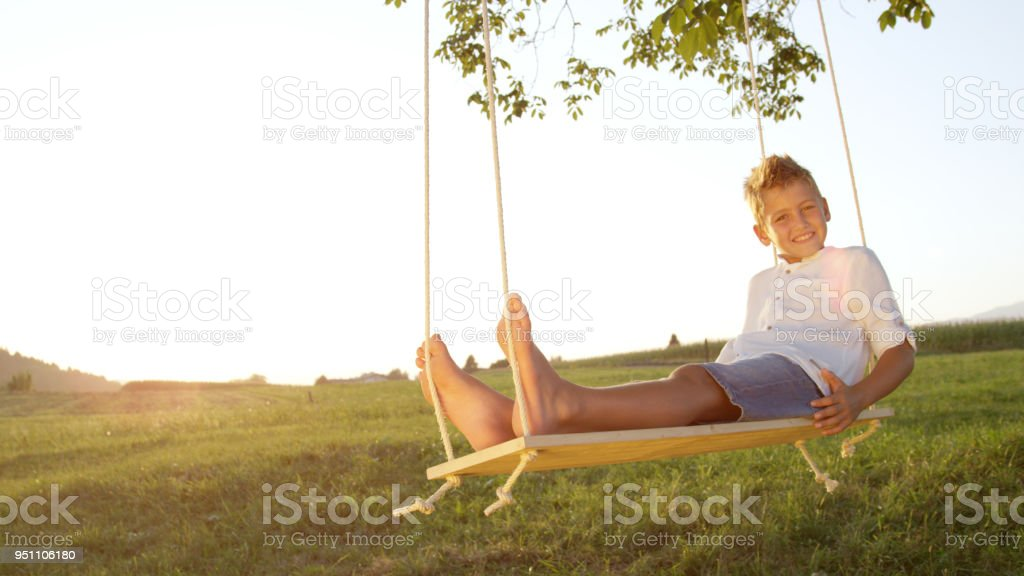 CLOSE UP Youngster relaxing on a wooden swing at sunset, posing for the camera. stock photo