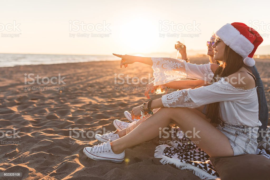 Youngsters in santa hats on the beach in the sunset stock photo