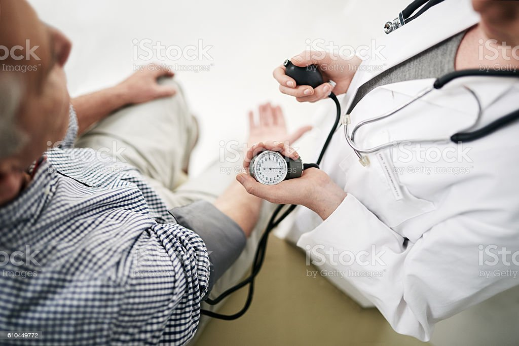 Your blood pressure is a little high... Shot of a doctor checking a senior patient's blood pressure in her office Adult Stock Photo