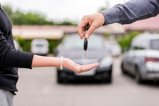 transportation and ownership concept - customer and salesman with car key outside. Woman at a car dealership buying an auto, the sales rep giving her the key, macro shot with focus on hands and key