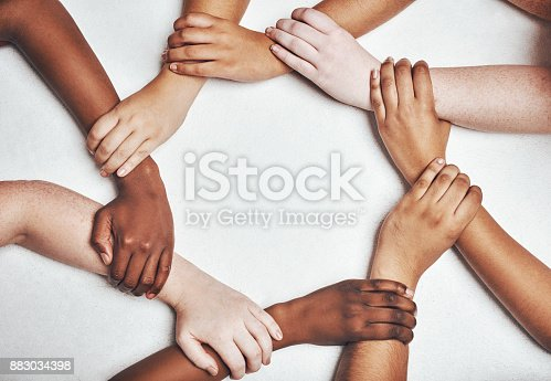 Shot of a group of hands holding on to each other against a white background