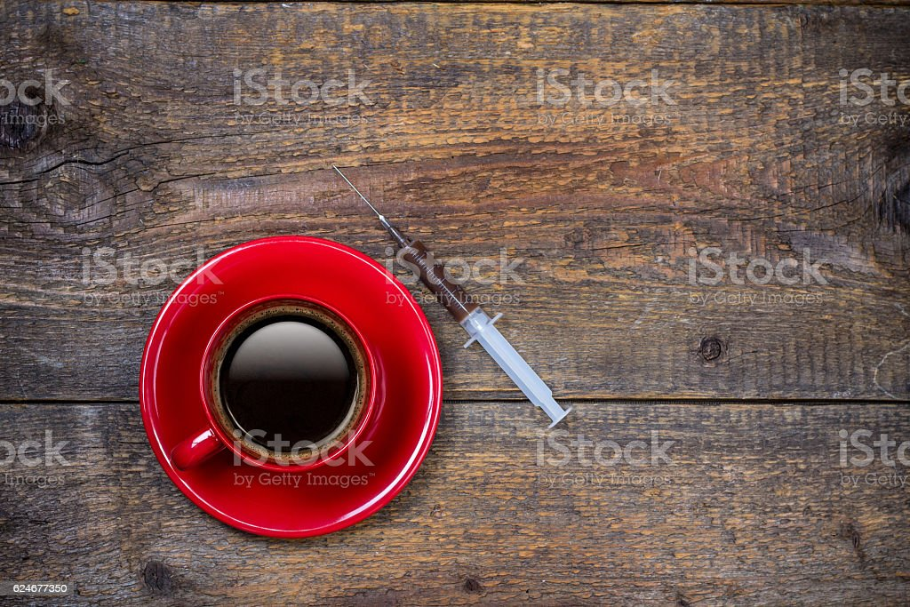 Your daily shot of coffee with cup and syringe stock photo
